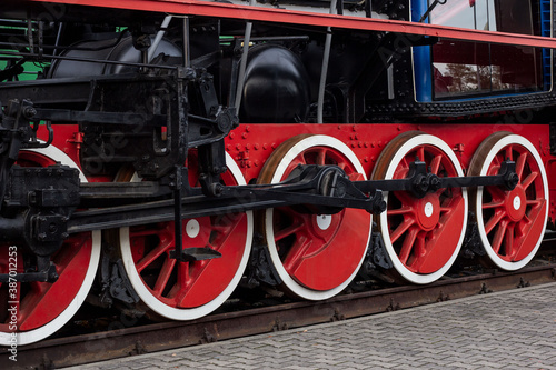 Old black and red retro steam locomotive wheels at the railway station. Vintage train staying on the railroad.