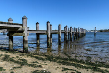 Long Dock With Pilings At Low Tide And Seaweed In The Foreground Against A Blue Sky.
