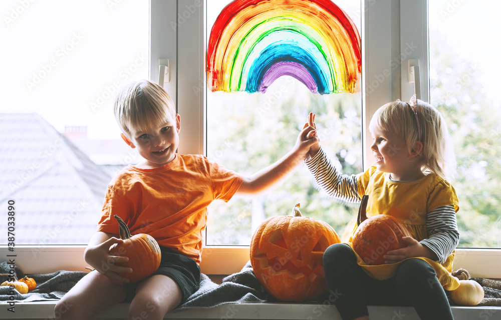 Fototapeta Preschool children on background of painting rainbow on window.  Family preparing for celebrating Halloween during quarantine Pandemic Coronavirus Covid-19 at home. Kids leisure activities indoors.