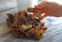 Hand Holding A Boiled Peanut Over A Table With Empty Peanut Shells