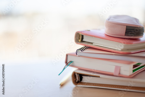 Photo stylish designed coral and white coloured stack of diaries with gold pen