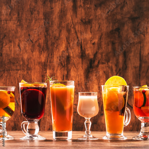 Obraz Selection of autumn or winter alcoholic hot drinks and cocktails - mulled wine, glogg, grog, eggnog, warm ginger ale, hot buttered rum, punch, mulled apple cider on wood background, copy space - fototapety do salonu