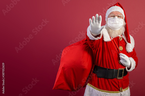 Obraz Real Santa Claus on red background, wearing protective mask and with an open hand in front making a pandemic stop sign. Christmas with social distance. Covid-19 - fototapety do salonu