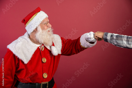 Obraz Real Santa Claus with red background, wearing glasses and hat doing elbow salute. Christmas with social distance. Covid-19 - fototapety do salonu