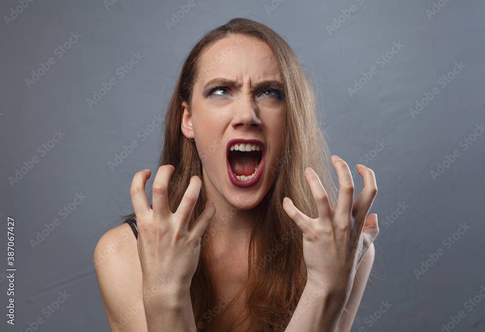Fototapeta Photo of angry woman with bright make-up on grey background