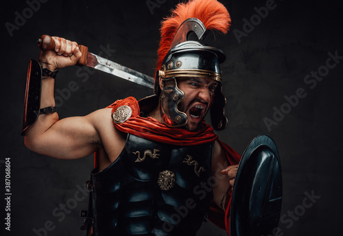 Canvas Print Attacking savage and brutal imperial soldier from rome in steel armour and red cloak holding sword and shield in dark background