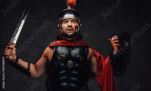 Fototapeta Brutal roman champion in dark armour with helmet and red cloak poses holding his sword and shield in dark background