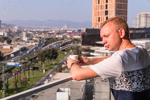 Man stays on balcony with cup of tea or coffee watching urban view of highway ro Canvas Print