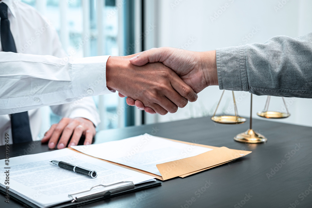 Fototapeta Male lawyer shaking hands with client after good deal negotiation cooperation meeting in courtroom