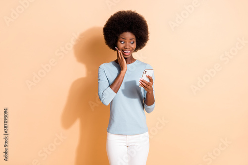 Obraz Photo portrait of shocked impressed dark skinned girl reading information from smartphone touching face with hand isolated on beige color background - fototapety do salonu