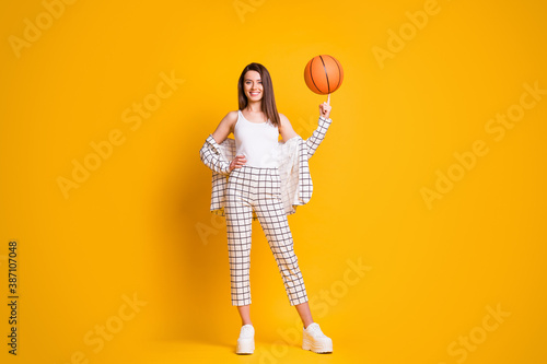 Obraz Photo of nice attractive sportive brown hair woman spinning ball playing basketball isolated over bright yellow color background - fototapety do salonu