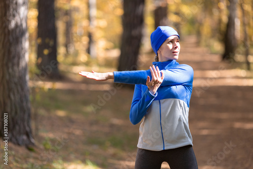 Fotografie, Tablou Caucasian adult woman in blue sportswear and a cap warm up her triceps and joint