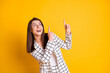Photo of amazed business woman dressed checkered blazer pointing looking empty space two fingers isolated yellow color background
