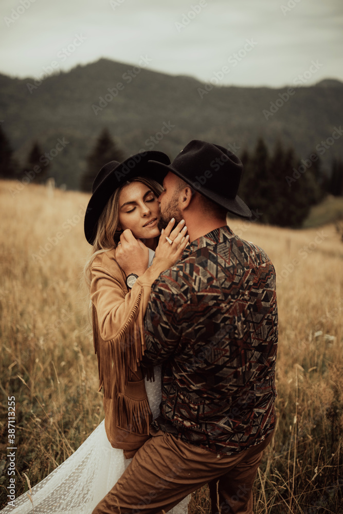 Fototapeta Stylish young and beautiful couple  photographed outdoors in the mountains at their elopement.