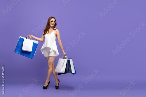Obraz Fashionable Asian woman carrying shopping bags and walking on purple isolated studio background - fototapety do salonu
