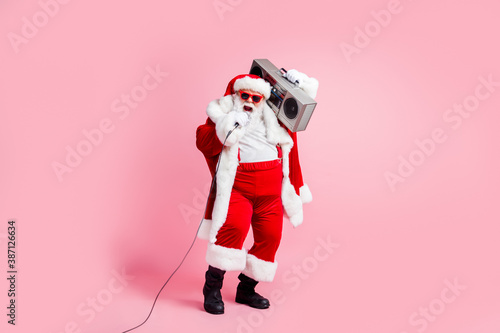 Obraz Full length photo cool crazy grey white hair beard santa claus big belly sing x-mas christmas eve noel song hold boom box mic wear suspenders cap sunglass isolated pink color background - fototapety do salonu