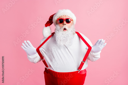 Obraz Photo of astonished overweight santa claus impressed tradition x-mas christmas shopping sales news pull suspenders wear headwear overalls sunglass isolated pink color background - fototapety do salonu