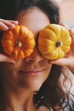 Portrait Of A Young Woman Smiling With Small Pumpkins On Her Face