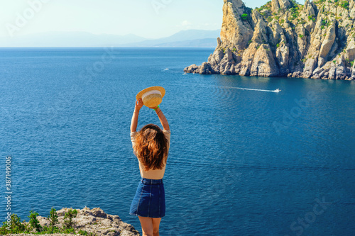 Fotomural Happy young woman holding a hat and running down the mountainside with a view of the rocks and the sea