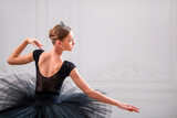 portrait of a young ballerina in black tutu, view from the back