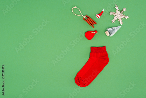 Obraz na plátně top view of red christmas stocking near festive baubles on green background with