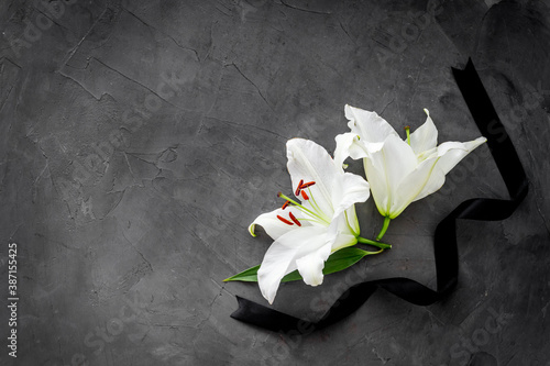 Fotografering Funeral symbols. White lily with black ribbon, top view