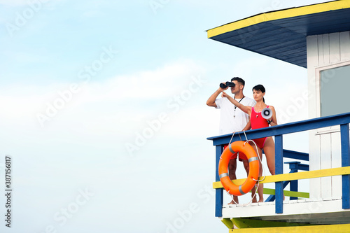 Fototapeta Lifeguards with megaphone and binocular on watch tower against blue sky