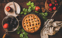 Autumn Tea Time Setting. Flat-lay Of Seasonal Whole Baked Apple And Plum Homemade Pie On Rack With Tea In Pot Over Dark Rusty Table Background, Top View. Fall Sweet Comfort Food Concept