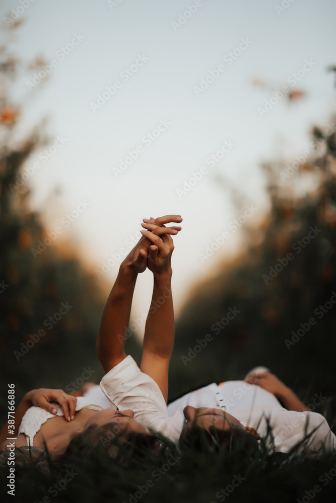 Fototapeta Young couple lying on green lawn while spending time together in park. Romantic atmosphere. They holding hands.