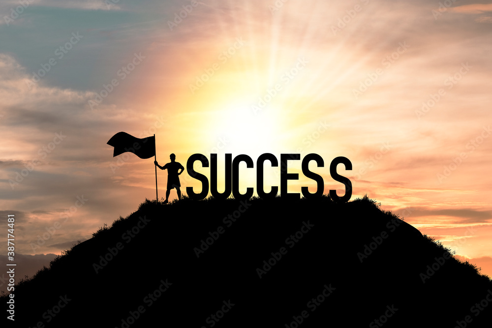 Fototapeta Silhouette business man standing and holding flag with success wording on the top of mountain, business success and achievement objective target concept.