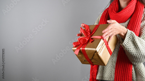 Girl holding a gift with a red ribbon Fotobehang