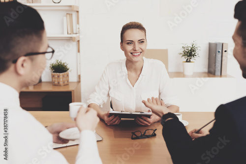Obraz Two men are interviewing a woman sitting at table. - fototapety do salonu