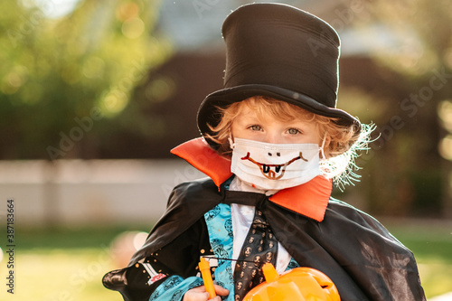 Obraz Happy Halloween. A child in a medical mask in a dracula costume sits on a pumpkin in his yard. - fototapety do salonu