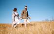 Stylish  young couple enjoying autumn weather in autumn field. Lovely couple walking and hugging in the field together. The concept of youth, love and lifestyle.