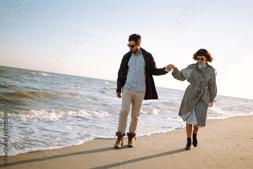 Young loving couple walking and hugging by the sea Fototapet