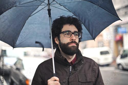 Obraz na plátne young man with umbrella inn the street