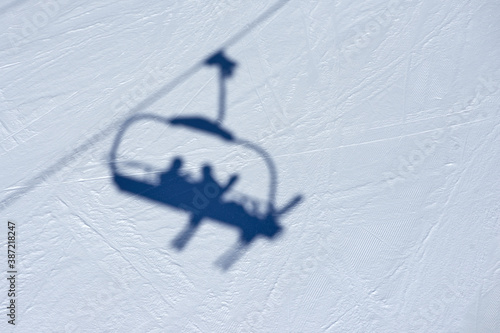 Obraz na plátně Shadow of the ski lift chair with skiers on the snowy piste surface near Tignes high-altitude resort in France during the winter season
