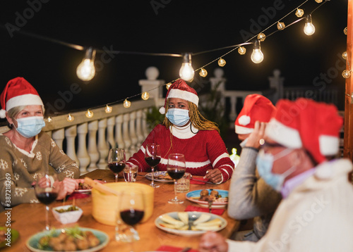 Photo Multiracial senior people celebrate christmas together with dinner outdoor while