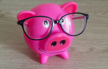 Piggy Bank And Glasses On Wood...