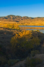 The Warm Glow Of The Morning Sun Bathes The Top Of Autumn Trees And The Distant Mountains On A Chilly October Morning At Chatfield Lake In Colorado.