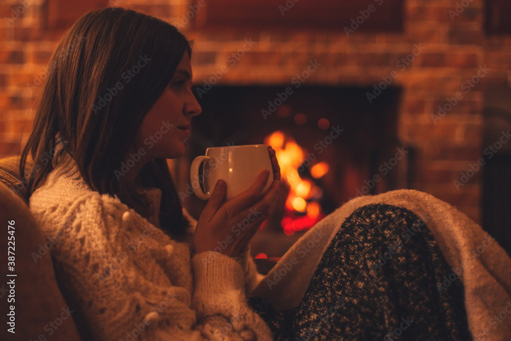 Fototapeta Young woman wearing white woolen knitted sweater enjoying hot tea near fireplace in a cozy living room.