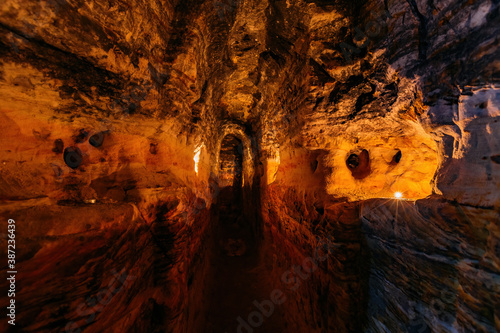Ancient narrow underground passage in sandstone at old underground monastery Fototapeta