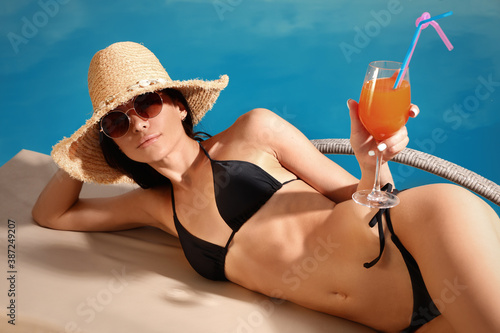 Young woman in stylish black bikini with cocktail near swimming pool