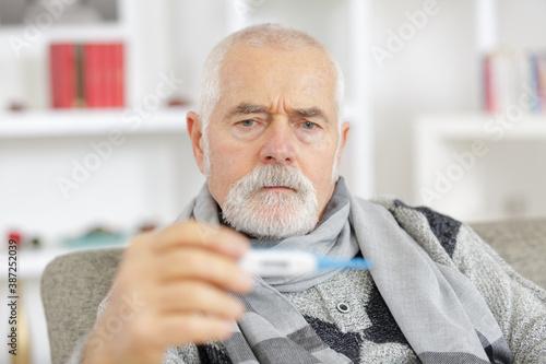 Obraz sick senior man in scarf holding thermometer at home - fototapety do salonu