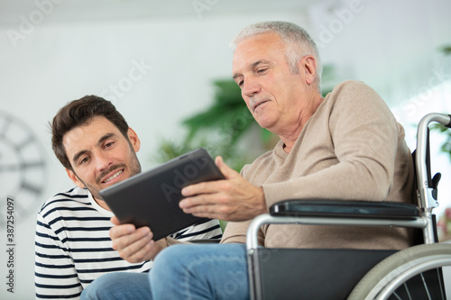 Fotografia man in wheelchair showing tablet to male companion