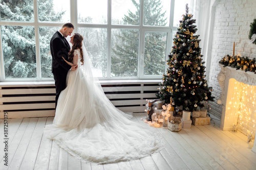 Obraz Young couple in love bride and groom posing in studio on background decorated with Christmas tree in their wedding day at Christmas near the large panoramic window. - fototapety do salonu