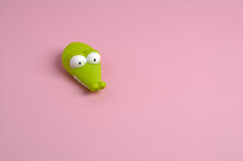 Detail Of A Green Plastic Crocodile With Round White Eyes On A Smooth Pink Background