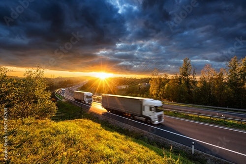 Obraz Three motion blurred trucks driving on the asphalt highway in forested landscape in the golden rays of the sunset with dark cloud - fototapety do salonu