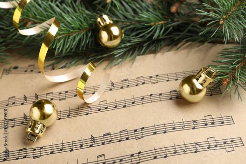 Fir branches, golden streamer and balls on Christmas music sheets, closeup