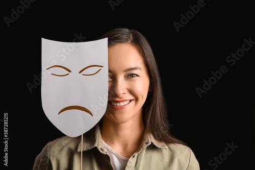 Valokuva Happy actress with sad mask on dark background